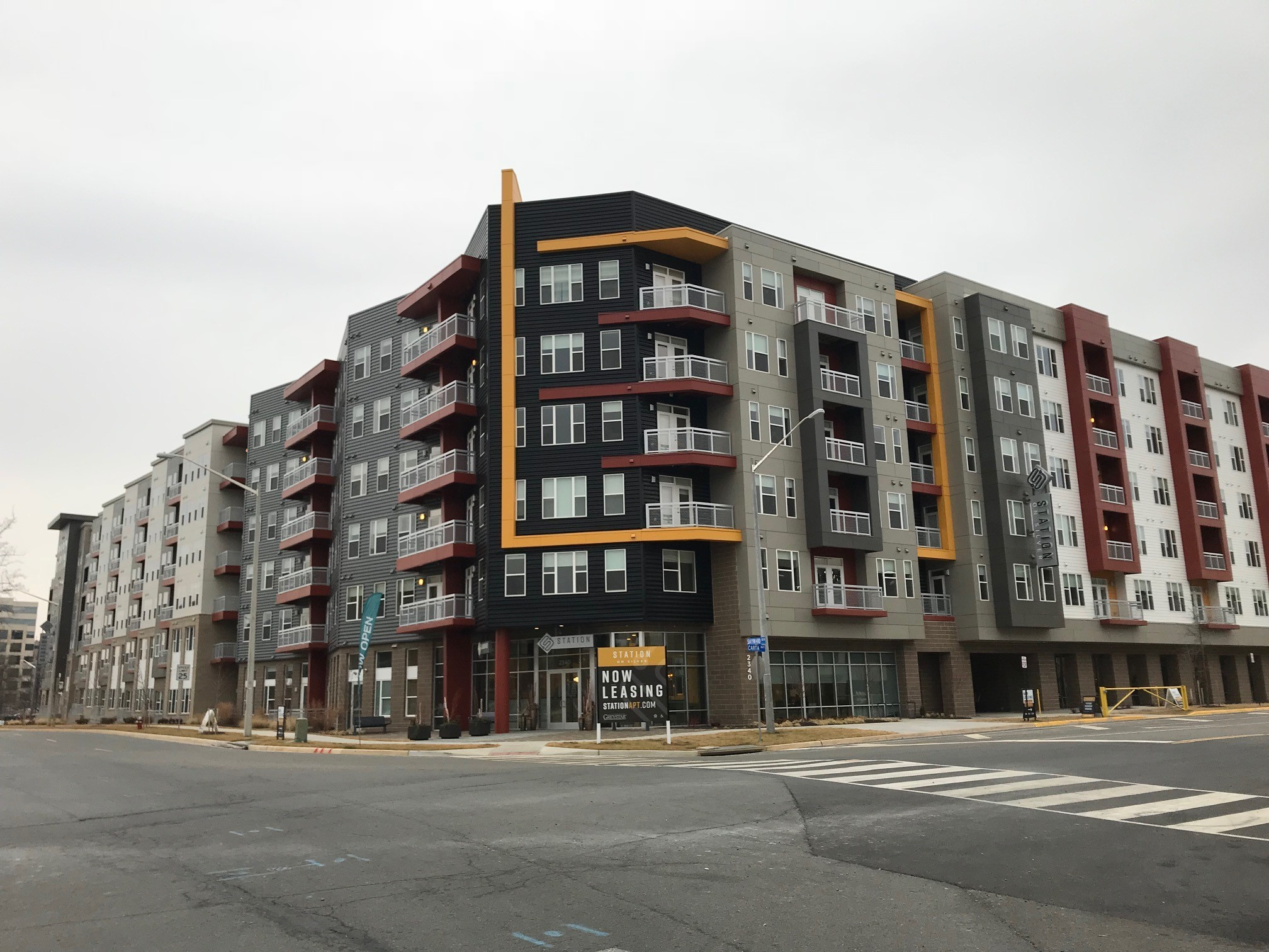 Dulles Station Parcel apartment complex in Virginia as seen from the street with a 'now leasing' sign.